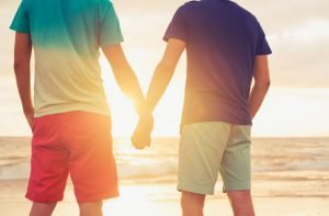 Happy gay couple holding hands watching sunset on the beach